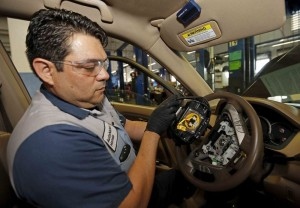 File photo of Technician Bonilla holding a recalled Takata airbag inflator after he removed it from a Honda Pilot at the AutoNation Honda dealership service department in Miami